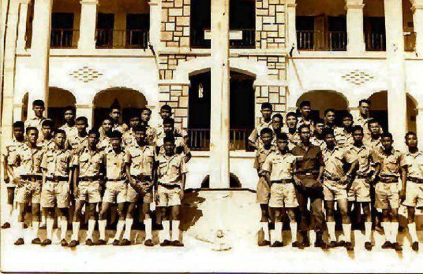 Cán bộ và thiếu sinh quân dưới cột cờ vàng.