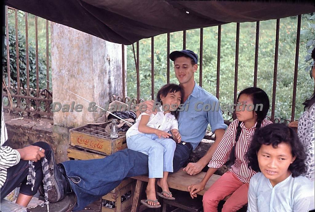 Một quầy giải khát vỉa hè cùng anh khách tây và trẻ em Việt, sự thân thiện được biểu hiện rõ bởi nụ cười trên môi