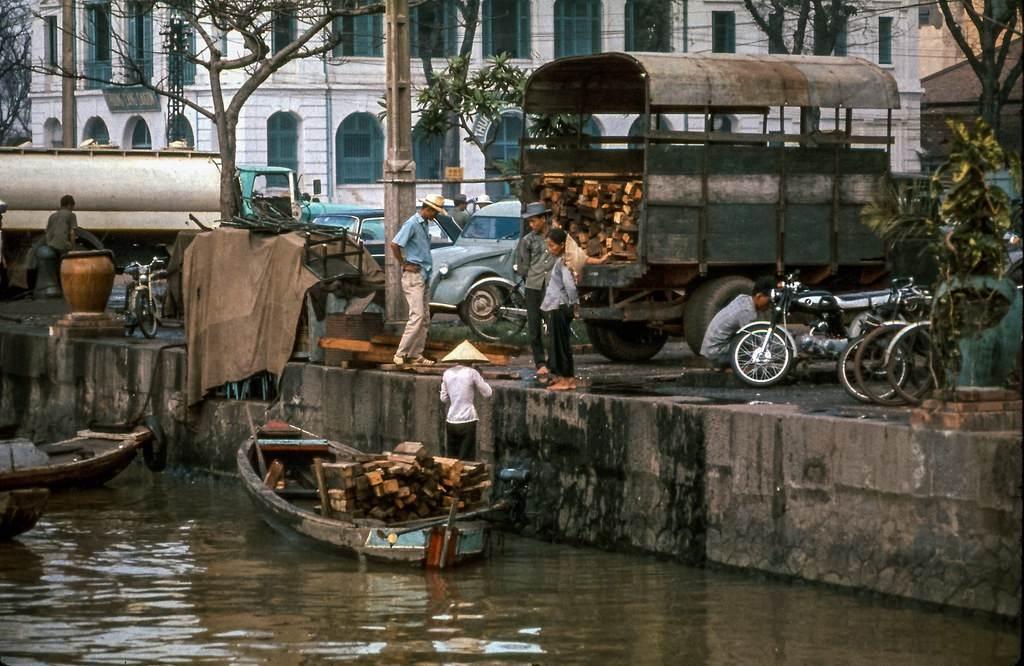Một chiếc thuyền chỡ gỗ bốc lên xe tải ở Bến Bạch Đằng, thập niên 1960