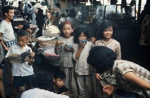 Em bé Sài Gòn xinh xắn, hồn nhiên ăn uống trong một khu chợ xưa.