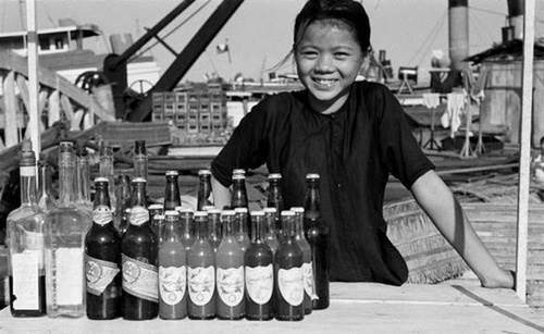 Nụ cười hồn nhiên của cô bé bán nước bên bờ kênh.