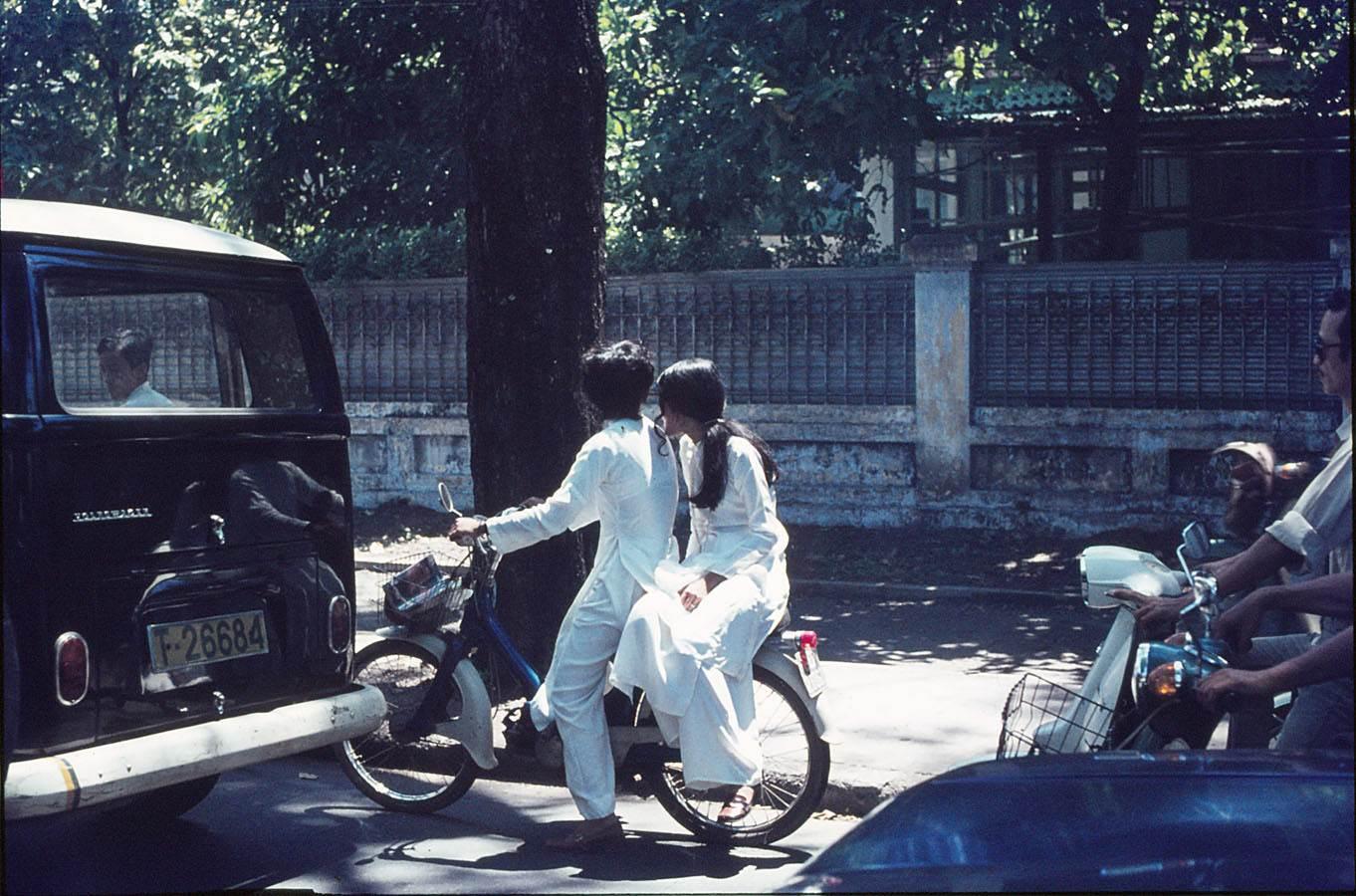 Hai thiếu nữ đang chở nhau trên đường. Cô gái ngồi sau ngồi phong cách một bên