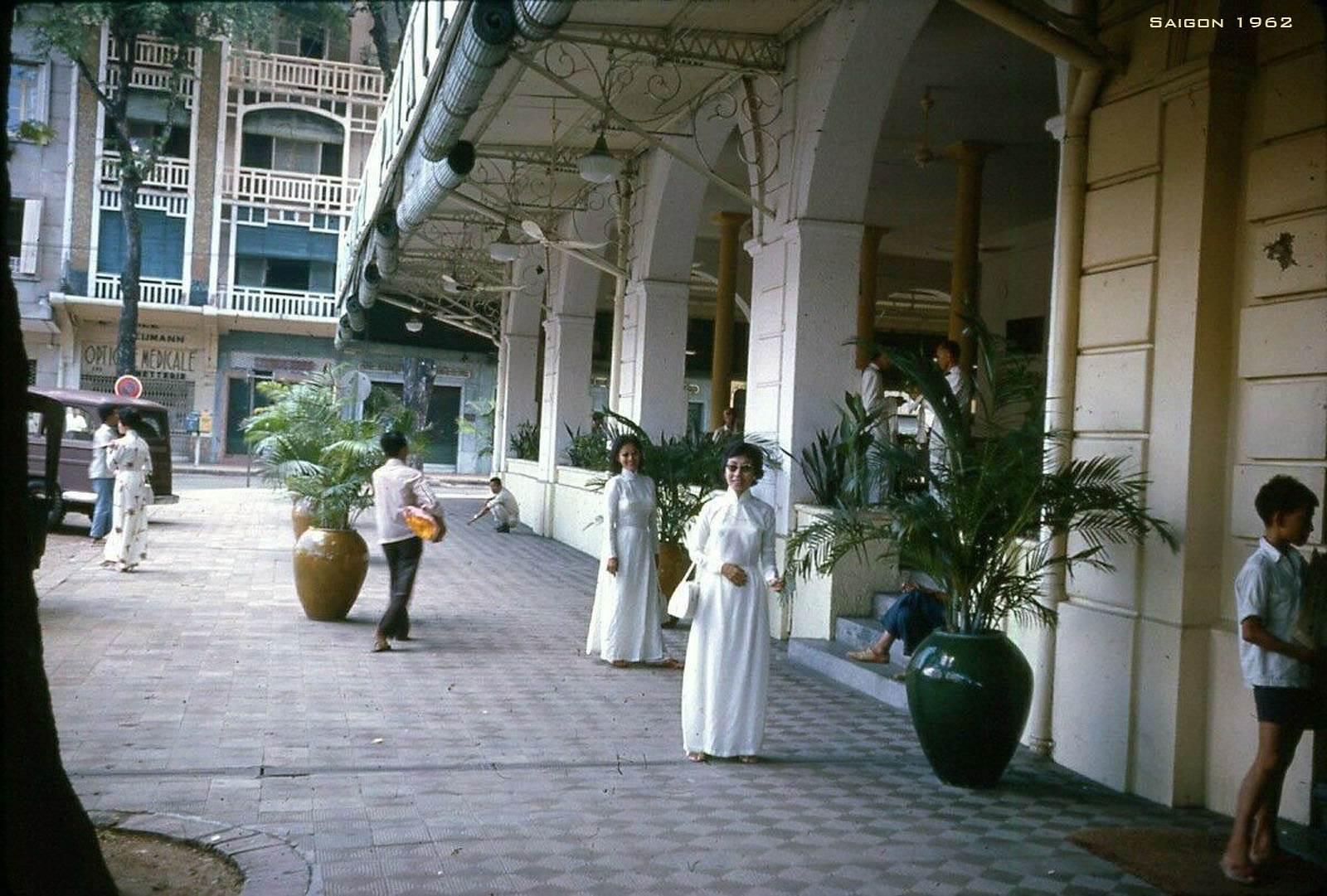 Hai phụ nữ mặc áo dài đứng trước khách sạn Continental