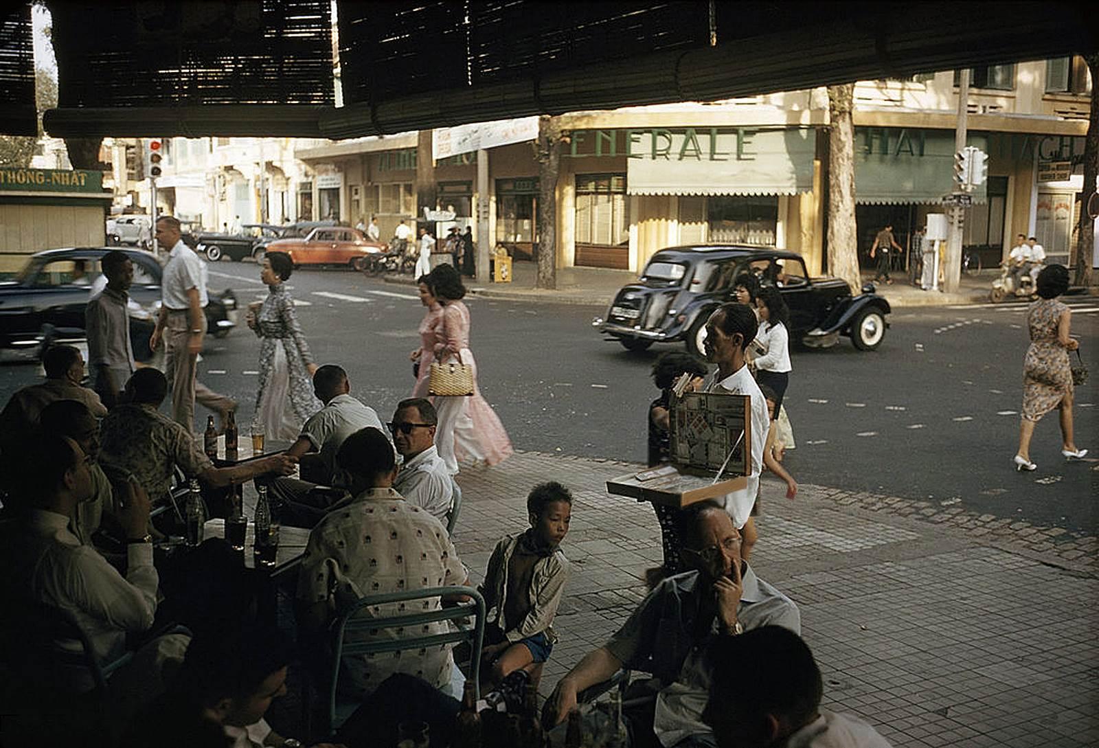 Những khách hàng nam giới của một tiệm cà phê vỉa hè trên đường Tự Do (Đồng Khởi) ngồi ngắm quý bà quý cô qua lại trên đường.