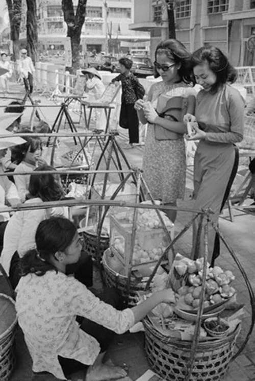 Hai thiếu nữ tản bộ dừng lại mua chút đồ ăn vặt bên vỉa hè