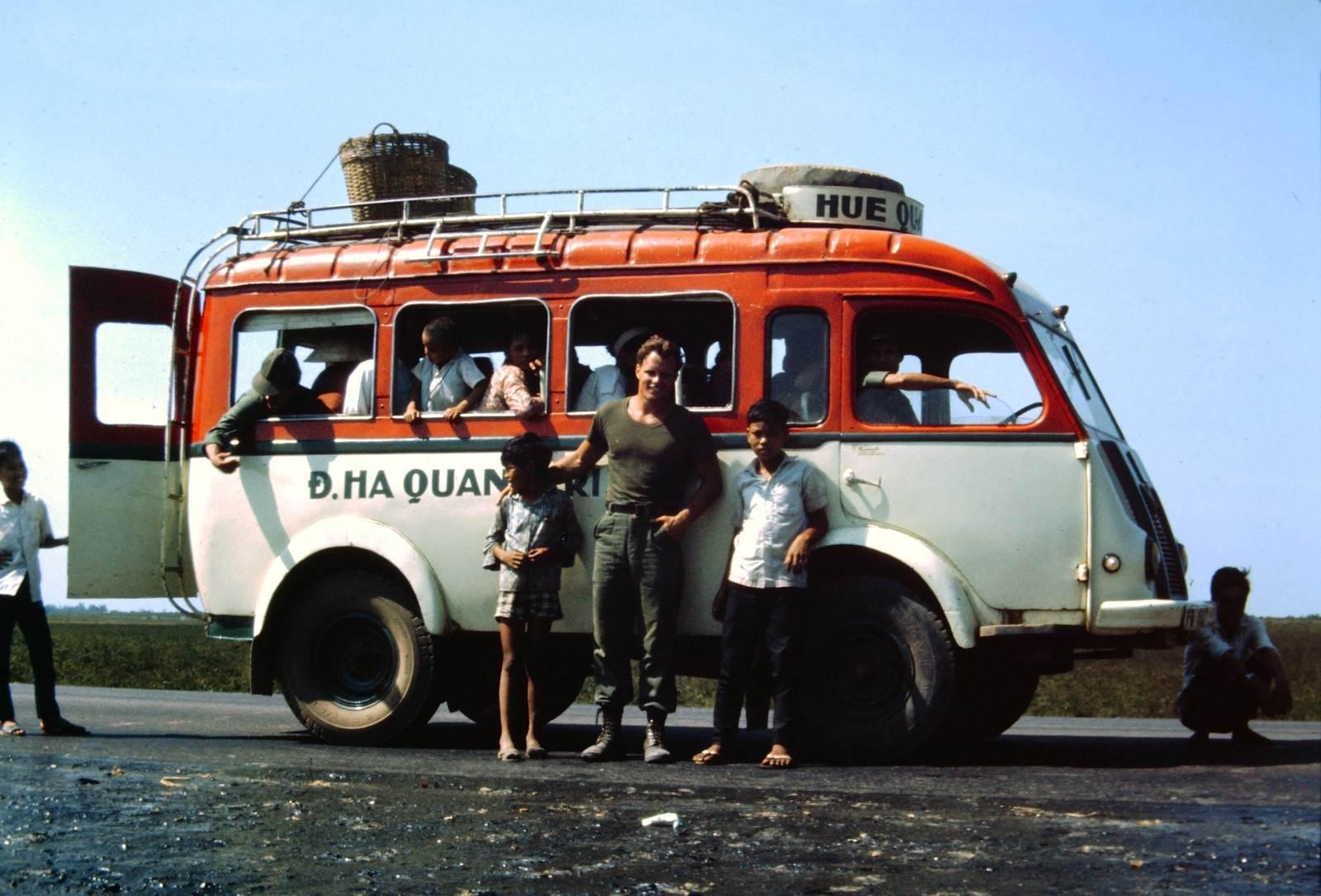 Một người Mỹ đang tạo dáng cùng hai đứa trẻ Việt trước xe khách Đông Hà - Quảng Trị