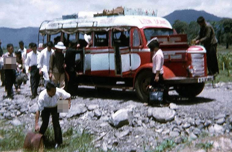 Xe khách đang dừng lại để hành khách xuống xe, trong lúc đó bác tài đang kiểm tra lại xe