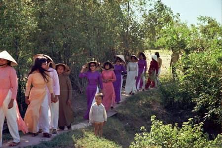Cô dâu là người mặc áo hồng, đi giữa hai phụ nữ mặc áo dài tím.