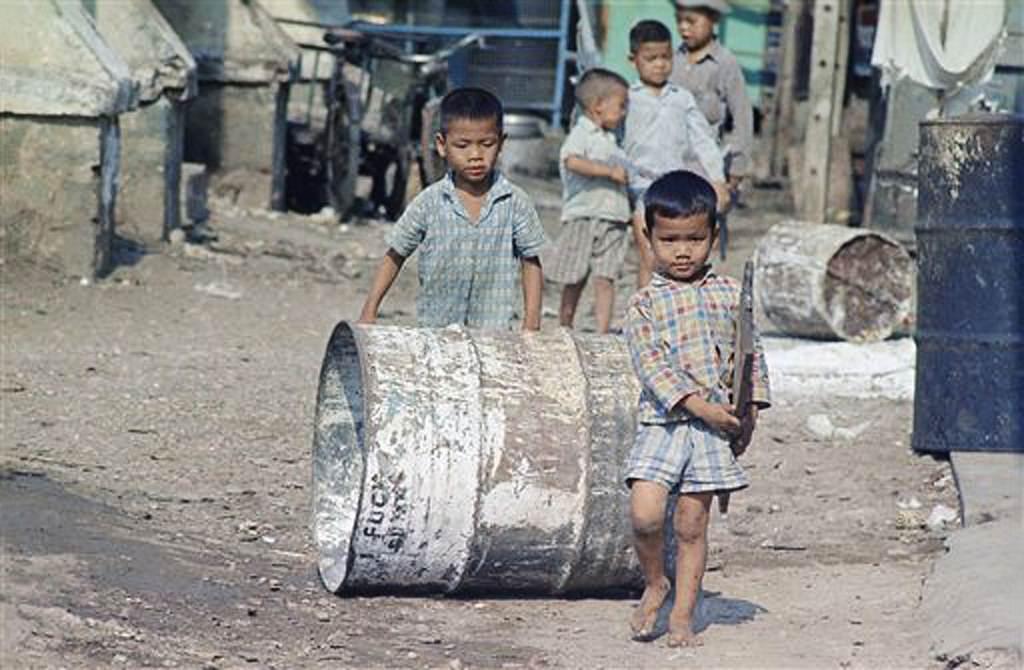 Hai cậu bé vận chuyển một tấm ván và một cái trống thép đến nghĩa trang nơi họ sống cùng gia đình, tháng 4 năm 1968. Những người nghèo nhất Sài Gòn đã phải xây nhà ở nghĩa trang địa phương. (Ảnh AP / Eddie Adams)