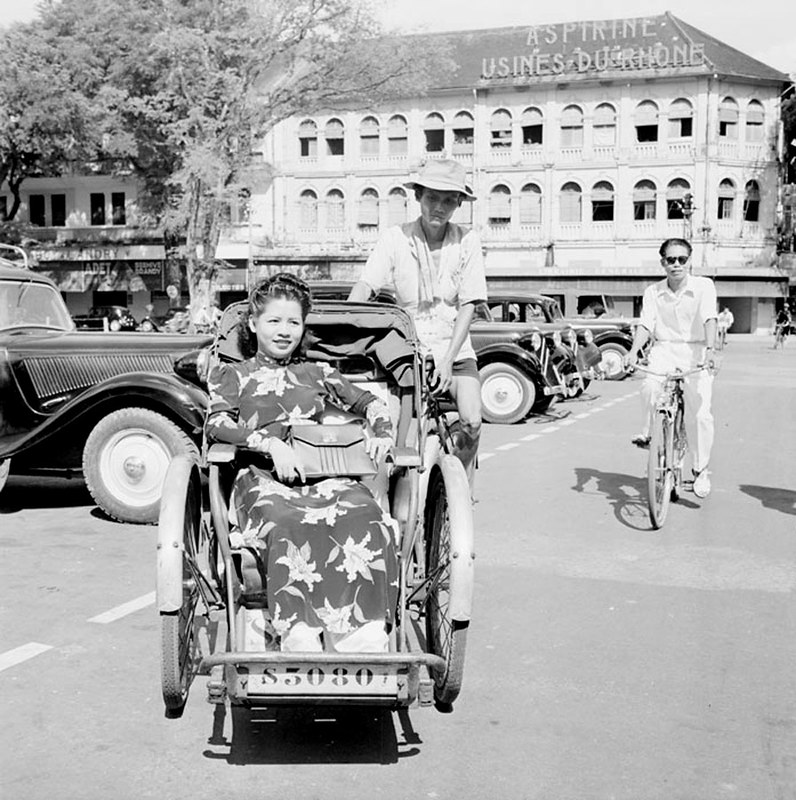 Sài Gòn 1950. Một người phụ nữ với chiếc áo dài hoa văn thanh lịch trên chiếc xe xích lô.Phía sau là nhà hát TP.